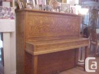 The piano is an oak Heinzman upright grand from the