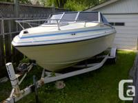 Boat is in fair condition, on a yaht club trailer with