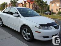 4 door white Sedan, grey interior, with spoiler Female