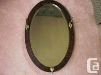 This is an antique mirror. It has an oval oak frame and
