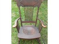 Antique pressed back rocker with leather seat. Lion's