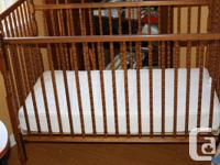 Good condition baby crib with a mattress and a crib set