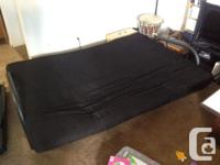 Simple black futon. Seats 3 people comfortably and