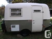 A 1973 white and green fiberglass Boler travel trailer