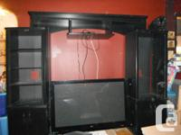 BLACK ENJOYMENT CENTER/WALL DEVICE. WE HAD OUR 60 INCH
