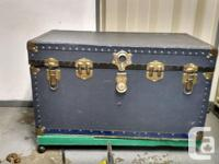 Classic navy blue trunk with brass fittings. Has a lock