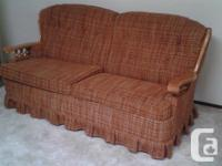 Couch has wooden armrests delicately made use of.