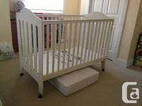 A white crib is in a good condition, bed and mattress.