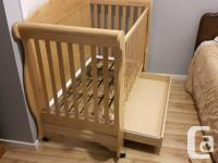Wooden crib with front side that can slide down. Has 2