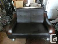 A dark brown leather chair and love seat both with