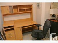 Wood desk with keyboard tray and office chair. Lots of