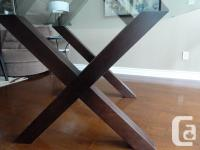 table has a solid wood base and tempered glass