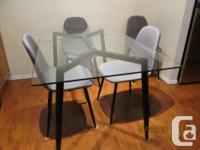 A modern, minimalist dining set was bought new, full