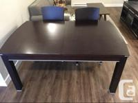 Dark brown dining table with 6 chairs. Table easily