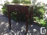 Sewing table with a hinged top that flips out to the