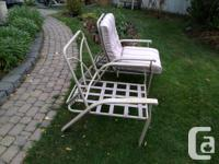 4 steel patio chairs, one with cushions, three without.