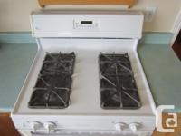 White, 30 inch gas range. Four burner stove top, self