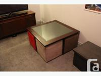 This is a wooden framed, glass top coffee table, about