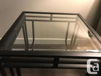 Two glass top end tables with a black metal frame.
