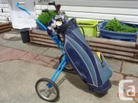 Blue bag on wheels. Clubs include#1,234 Woods. Steel