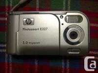 This is an HP PhotoSmart E327 5MP digital camera. It