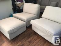 Two cream colored Ikea Kivik chairs with matching