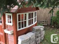 Kids cedar playhouse with white trim and flower boxes