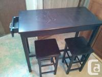 Dark brown table is rectangle with a small drawer on