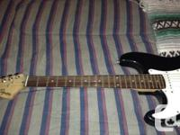 Its a black left handed stratocaster squier guitar that