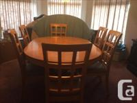 This maple dining room table includes 6 chairs and a