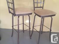 2 matching swivel bar stools with padded seats. Metal