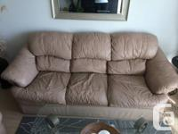Neutral beige leather-made couch and matching chair.