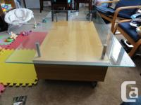 I'm looking to sell a nice glass coffee table on wheels
