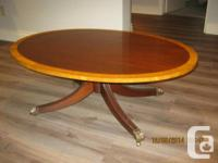 Coffee table having oval top with inlaid border, in