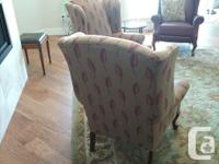 Matched pair of wingback chairs. Mahogany legs.
