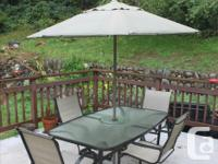 Glass top patio table and four chairs, with umbrella.