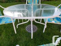 Table, chairs, umbrella and umbrella stand. Cushions