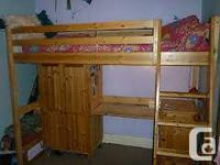 A bed with an appropriate size ladder along with a desk