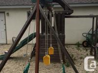 Wooden play structure with swings, slide, monkey bars,