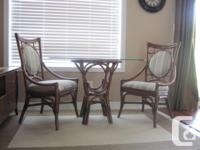 Dark brown rattan table and with 2 high back chairs.