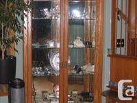 Firm. Large, simple, wood and glass cabinet; mirrored