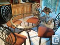 The kitchen table has a glass top and metal frame. It