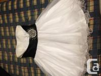 White gown with black sash and rhinestone decorations.