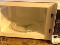 Small white microwave with black button pad. Was only