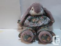 Brown and white bunny is wearing a pink floral on dark