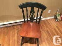 Rectangular solid oak table with dark green pedestal.
