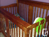 Camel coloured convertible solid wood crib. Slight wear