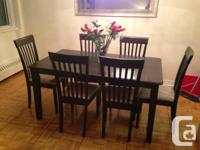 Dark brown wood table with 6 chairs that have a beige