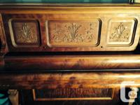 This beautiful antique upright piano was refinished