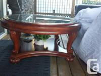 . Round, brownish, polished, glass coffee table on